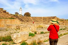 Cyprus Pafos Odeon. A small 2nd century Odeon built entirely of well-hewn limestone blocks used nowadays for musical and theatrical performances. And in the back the beautiful 20m-high whitewashed Pafos lighthouse.
