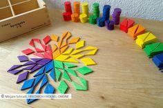 Spielidee mit geometrischen Formen:  Mandala, das ausschließlich aus geichschenklig-stumpfwinkligen Dreiecken besteht, die zu Rauten zusammengefügt wurden, in den 6 Farben des Regenbogens gelegt