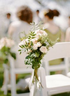 Clusters of ivory spray roses, seeded eucalyptus, magnolia foliage, and bay laurel will be tied to the sides of the aisle chairs