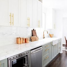 Airy and white kitchen with gold and copper accents, white marble countertops, and mint green cabinets.