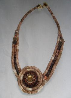 Colar com 3 cordas cobertas com fita mesclada e fita marrom, aplicação de medalhão também de corda coberta e aplicação de strass e botões. Acabamento dourado R$ 24,00