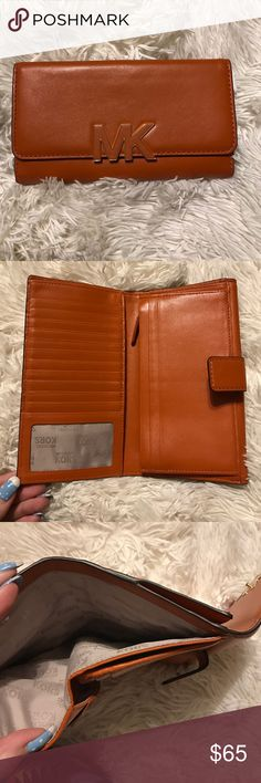 Michael Kors wallet Orange Michael Kors wallet. Not sure the style name - but it's amazing! So many pockets and places for cards. Slight use from being in a purse, but overall great condition. Matches perfectly with the Jet Set tote being sold. Michael Kors Accessories Watches