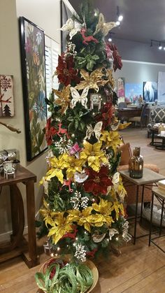 Traditional tree full of poinsettias. Foliage is a good way to make your tree feel fuller. www.interiorsonmain.com