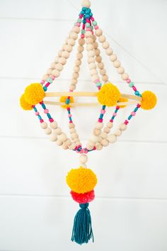 DIY Wood Bead Pom Pom Chandelier is easy to make with a few craft supplies from JOANN and these steps. Yarn pops, wood beads and this tutorial Dollar Store Crafts, Crafts To Sell, Diy And Crafts, Arts And Crafts, Sell Diy, Diy Design, Home Design, Vitrine Design, Pom Pom Mobile