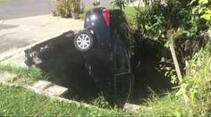 A car lies vertically after falling down into a sinkhole