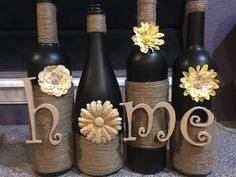 Beautiful wine bottle decor Painted black and accented with twine and letters that spell out home. Love the yellow floral accents.