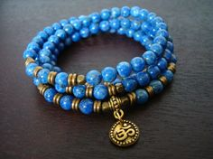 """denim lapis shakti om mala, made with a rare shade of denim lapis lazuli and gold or silver om charm. lapis is known as the """"stone of total"""