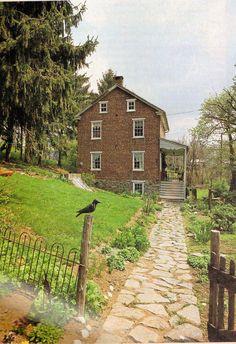 cobblestone path; low metal fence; side garden