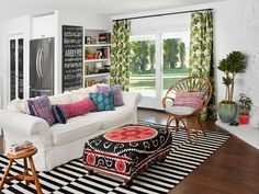 """Amber furnished the living room space with a striped rug, a rattan chair, a suzani-covered ottoman and a white slipcovered sofa piled high with bright pillows. """"I stick with neutrals for the stuff that's hard to change, like upholstered pieces and walls,"""" she says. (Striped 7'10"""" x 5'7"""" rug by Stockholm Rand flat-woven from IKEA)"""
