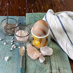 Single egg in an egg cup on a wooden surface with an assortment of crystal Himalayan pink salt and pepper. Olive decorative reef in the background. Stock Image.