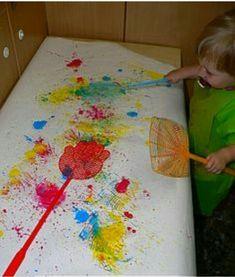 De peuters kunnen met verf en een vliegenvanger leuke dingen maken op een schilderij.