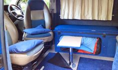 Side folding bed rests on small table and swiveled front seats