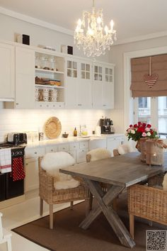 ~earthy colors~kitchen decor~white cabinets, wicker chairs, wooden dining table, chandelier, and natural colored window shade~ Eclectic Kitchen, Modern Kitchen Design, Kitchen Interior, Kitchen Dinning, New Kitchen, Kitchen Decor, Kitchen Island, Dining Room, Beautiful Kitchens