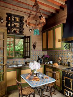 Designer Jacques Grange updated Pierre Bergé's country home in Normandy, France. A 19th-century Eastern European light fixture hangs in the kitchen, antique French tiles pave the backsplash, and the range and hood are by La Cornue.