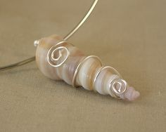 Wire Wrapped Sea Shell Pendant. I think I'd do it with the wire spiraling with the shell, not against.