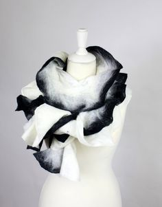 It is a regular wave scarf with some black edging. This is the narrow version of the regular one so it sits very nicely around the neck. The white