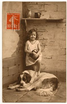 France circa 1915 - antique photo of a little girl with her huge dog.  Looks like this photo may have been taken in a basement.