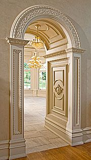 French Rineau scroll with 'Mon Reale Acanthus' crown molding is continued through each side of the archway walls. Two-insert radius with recessed rope panels accent the columned entrance through a 4-foot deep barrel-raised panel ceiling making an elegant entryway