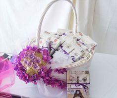 Canasta para regalos de boda, adornada con hortensias en tonos morados.El regalo es un bloc de notas de estilo vintage.