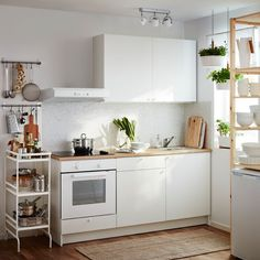 A small white kitchen consisting of a complete base cabinet with doors, drawers, worktop and a wall cabinet with doors. Combined with a white wall mounted extractor hood, an oven and a black glass ceramic hob. #Kitchenremodel #Paintedkitchencabinet #Kitchencountertops