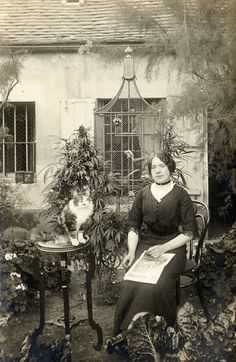 A woman, her cat, and birds. Early 20th C. from the look of it.