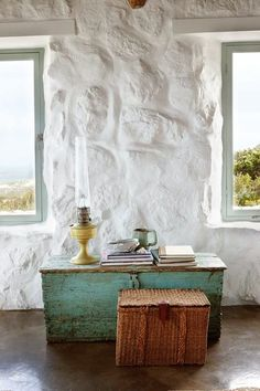 blue-green antique blanket chest in a seaside cottage with white-washed stone walls.
