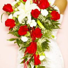 Cascading bouquets have a comcentration of blooms near the bride's hands.