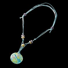 Delicate butterfly motif on light blue glass medallion with blue cotton strings and purple and yellow beads; adjustable; Child's necklace made in Chile