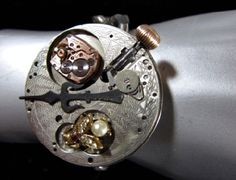 """A Quarter to Steampunk Bracelet""  Made with a beautifully engraved pocket watch movement part, a small watch movement, a vintage fly pin and a vintage clock hand.  All mounted on a vintage watch with a chunky metal chain band. $110"