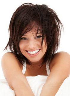 Cette jeune femme à l'air espiègle porte une coiffure qui convient magnifiquement bien à sa personnalité. Ses cheveux mi-longs ont été coupés en dégradé et le coiffeur a su leur donner un effet décoiffé vraiment chouette. La coloration brun foncé ajoute elle aussi beaucoup de dynamisme à la coiffure.