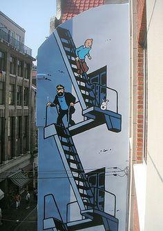 """-rue de l'Etuve 37- La fresque de Tintin d'après le héros de Hergé fut inaugurée le 20 juillet 2005, et aurait du être la toute dernière de la série, mais rien n'était moins vrai... Sa superficie est d'environ 35 m². Elle se trouve qu'à une bonne dizaine de mètres de cet autre Bruxellois célèbre, Manneken-Pis. Réalisation de G. Oreopoulos et D. Vandegeerde de la société """"Art Mural""""."""