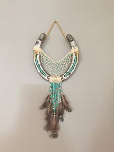 This is a horseshoe dreamcatcher with beautiful teal/turquoise and silver colored beads. Feathers that dangle from the beads and leather to hang on the wall. Please note that each horseshoe will vary slightly, as I make them to order. Thank you for looking! If you have any questions,