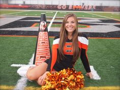 Cute pose for cheerleading portraits. Senior portrait with school megaphone and poms.
