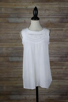 White tank with embroidered Aztec print neckline.