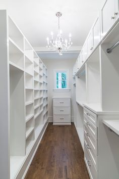 kate.h.design // Long and narrow closet space with white cabinets and Visual Comfort George chandelier.