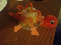 Dinosaur fruit cup treat! Easy to do and lots of different colors! One and a half pipe cleaners, one pom, two googley eyes, and four cut out feet from construction paper. A little hot glue and ta-da! We made these for my son's 4th birthday celebration at school. We went with 100% juice fruit cups, but you could use jello cups for more color.