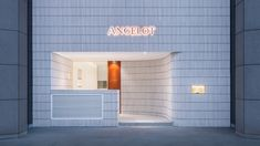 A sloping wall clad in white tiles hides the formerly problematic facade of Angelot patisserie in Hangzhou, China, designed by Say Architects. Tall Ceilings, Floor To Ceiling Windows, Public Architecture, Interior Architecture, Wall Logo, Stone Blocks, Natural Furniture, Orange Stone, Glass Boxes