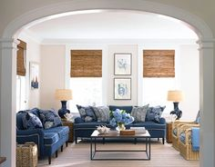 An All-American Family Room  Designed by Lynn Morgan, this family room features sofas covered in Florian Plain in dark blue from Cowtan & Tout. Throw pillows are China Seas Zig Zag and SeaCloth's Gypsy in Bloom. Ralph Lauren Cobalt Porcelain lamps sit on Pottery Barn rattan cubes.
