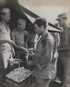 First Hot Chow for these rugged veterans of the bitter fighting on Peleliu, First Division Marines pass through the chow line and receive hot food for the first time in many days.