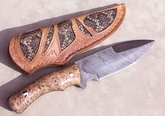 Damascus Tactical Master  1084 and 15n20 Damascus in a   Twist Pattern.  10 1/2 inches overall length with a 6 1/4 inch   bottom edge and 3 1/4 inch   top edge.  Handle in   this example is 100+ year old Birdseye Maple Burl.  Sheath is Top   Grain leather with Rattlesnake Skin Inlay