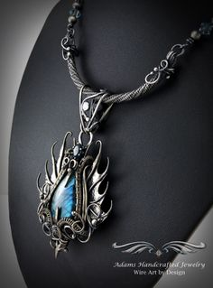 """""""Draco Tonitrui -- Once Upon a Time"""". Blue labradorite pendant with a one carat Swiss blue Topaz faceted gemstone. Fine .999 silver with handmade bar. Original design & creation by Daryl Adams."""