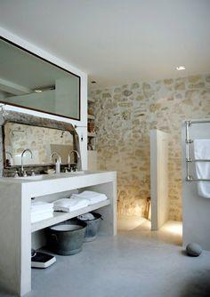reforma baño en apartamento rehabilitado con lavabos integrados en mueble de obra, zona de ducha con cerramiento de falsos tabiques, paredes de piedra, suelo microcemento.