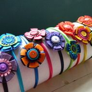 For beautiful girls of all ages!... These lovely hairbands are a universal size so are suitable for big girls and little girls alike! Each band has a large felt flower, with a button centre, which compliments the satin covered alice band. All of the co...