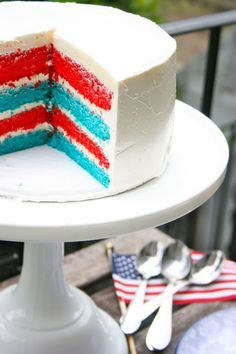 This 4-layer red, white, and blue cake is frosted with a white Swiss meringue buttercream.