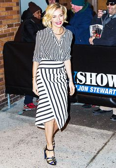 Sienna Miller in a black and white striped button-down tucked into a striped midi wrap skirt