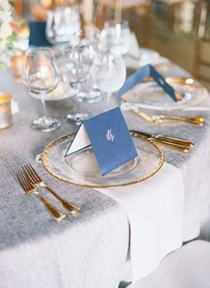 Stylish navy blue menu cards with grey table linens and gold cutlery.