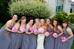 Bridesmaids in grey chiffon floor length gowns with a draped one shoulder neckline. They carried an array of shades of pink peonies.