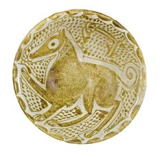AN ABBASID LUSTRE POTTERY BOWL DEPICTING A JACKAL OR CANINE, IRAQ, 10TH CENTURY    the earthenware body with slightly everted rim,painted in golden lustre on an opacified tin glazewith a canine figure probably a jackal with raised fore leg on a dotted ground with a single-lineinscription in foliated Kufic, stylised peacock eyesto the reverse  13cm. diam.