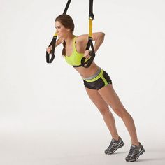 Stand facing away from the TRX with feet shoulder-width apart. Hold handles at chest height in front of you, arms extended and palms facing the floor. With body aligned from head to heels, shift weight to balls of feet, and bend elbows. Push up to return