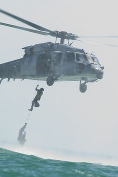 Navy divers using the latter of a SH-60B Seahawk.